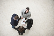 Portrait of young businessman standing on tiled floor with coworkers in a meeting - MASF06019
