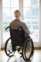 Rear view of disabled woman in wheelchair against french doors - MASF06028