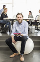 Portrait of mid adult businessman with digital tablet sitting on fitness ball in office - MASF06043