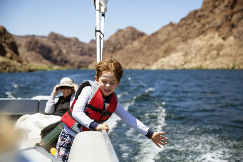 Happy boy traveling in boat with grandmother - CAVF44087