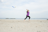 Girl playing with kite at beach against sky - CAVF44150