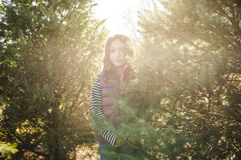 Portrait of girl standing amidst plants at park on sunny day - CAVF44171