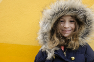 Portrait of girl in fur jacket against yellow wall - CAVF44174