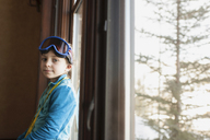 Portrait of girl with swimming goggles standing by window at home - CAVF44180