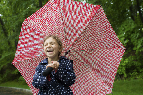 Girl laughing while holding umbrella at park - CAVF44201