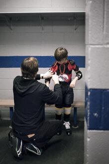 Father helping son with ice hockey uniform - CAVF44219
