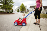 Mother pushing son in toy car - CAVF44225