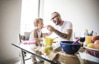 Happy father feeding daughter at breakfast table against brightly lit wall - CAVF44288