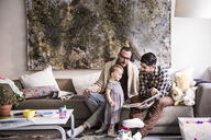 Fathers reading book to daughter while sitting on sofa at home - CAVF44297