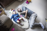 High angle view of happy father and daughter lying on floor at home - CAVF44312