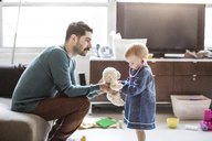 Father playing with daughter in brightly lit living room at home - CAVF44315