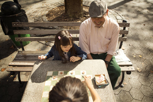 High angle view of grandfather looking at girls playing checkers game in park - CAVF44360
