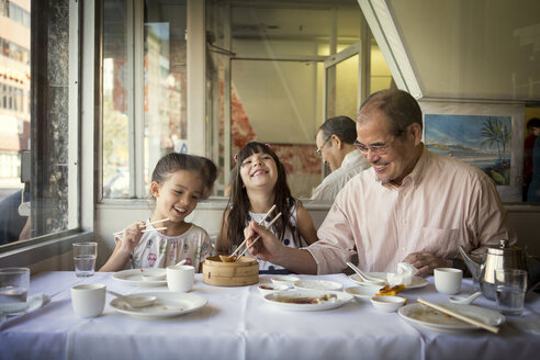 Happy family having food while sitting in restaurant - CAVF44375