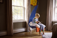Full length of boy reading book while sitting on swing in bedroom - CAVF44447