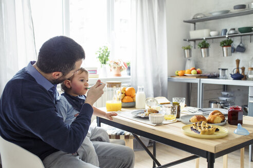 Father feeding breakfast to son at table in kitchen - CAVF44465