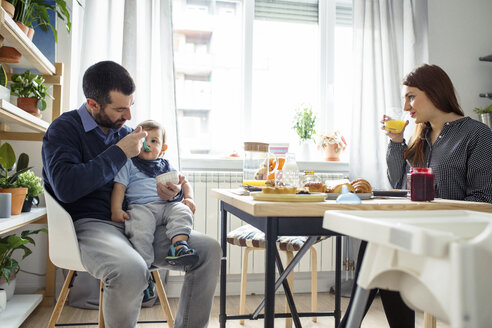 Woman looking at husband feeding son at table in kitchen - CAVF44468