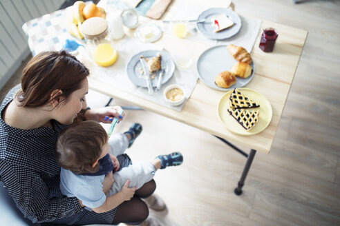 High angle view of mother feeding breakfast to son at table - CAVF44474