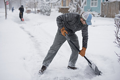 Man shoveling snow from street - CAVF44642