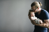Father kissing sleeping daughter while carrying her against gray background - CAVF44681