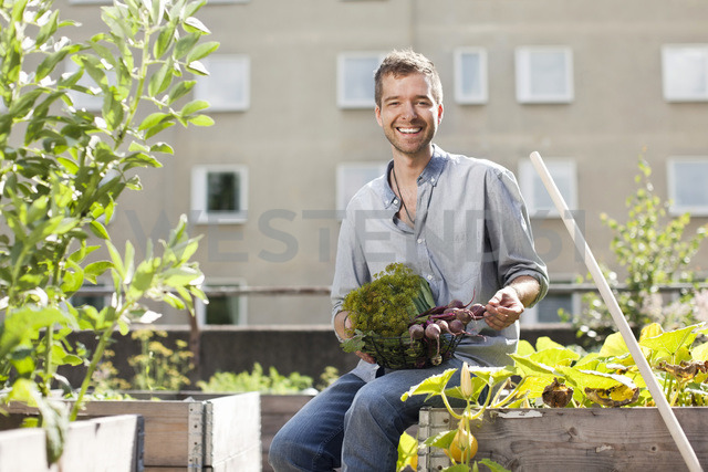 Portrait of happy young man sitting at urban garden - MASF06065