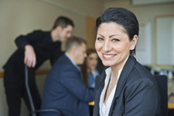 Portrait of happy mid adult businesswoman sitting against people in the meeting - MASF06083