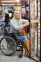 Portrait of happy disabled woman in wheelchair at refrigerated section of supermarket - MASF06098