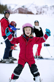 Portrait of happy girl enjoying skiing with family in background - MASF06110