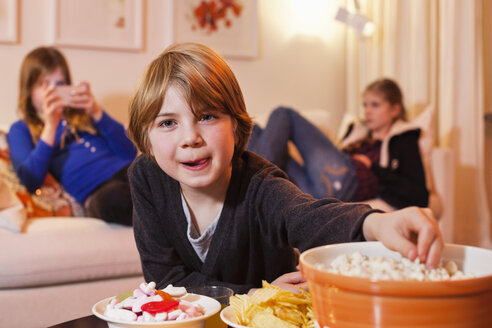 Portrait of little boy eating popcorn at coffee table with sisters in background - MASF06116