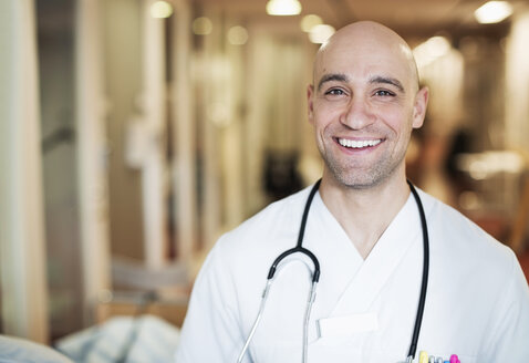 Portrait of happy mid adult male doctor standing in hospital - MASF06122