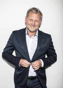 Portrait of mature businessman wearing suit while standing against wall - MASF06143