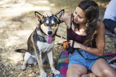 Smiling woman stroking dog while sitting at park - CAVF44705