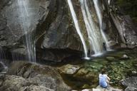 Rear view of woman sitting on rock against waterfalls - CAVF44774