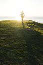 Rear view of woman walking on grassy hill by sea during sunset - CAVF44792
