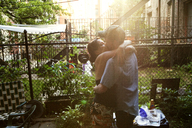 Affectionate couple kissing while standing in yard - CAVF44942