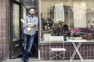 Portrait of confident mid adult male designer standing at studio entrance - MASF06188