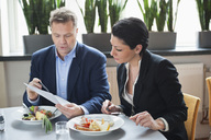 Mature businessman with female colleague discussing paperwork at restaurant table - MASF06227