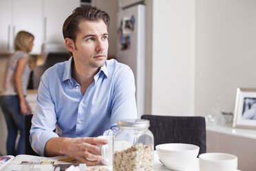 Mid adult man looking away while having coffee at table with woman in background - MASF06239