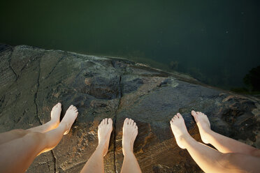 Low section of three people standing on cliff - MASF06263