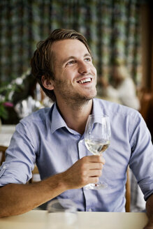Happy young man holding wine glass at restaurant table while looking up - MASF06275
