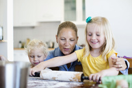 Happy woman looking at little daughter rolling dough on table in kitchen - MASF06335