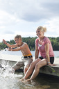 Happy mature woman sitting on pier with son splashing water - MASF06365