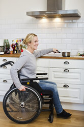 Happy disabled woman in wheelchair preparing tea at kitchen - MASF06374