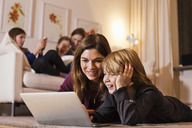 Happy mother and son using laptop on floor with family sitting on sofa in background - MASF06383