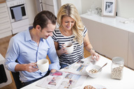 Happy couple with coffee cups reading property advertisements in newspaper at breakfast table - MASF06386