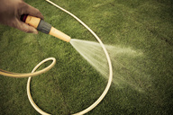 Cropped image of man's hand watering grass turf in lawn - MASF06416