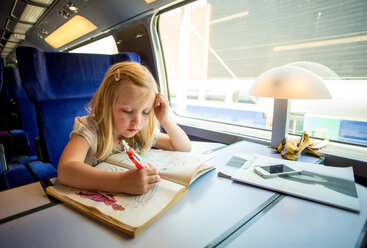Girl drawing pictures while sitting on train's seat - MASF06431
