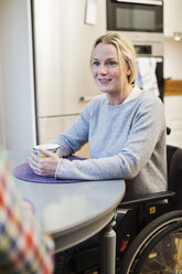 Disabled mid adult woman in wheelchair looking at friend in kitchen - MASF06440