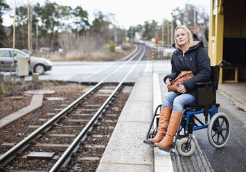 Disabled woman in wheelchair waiting for the train at railway station - MASF06443