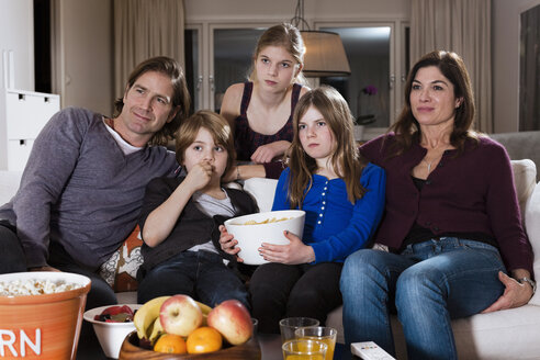 Family of five with bowl of chips watching television in living room - MASF06452