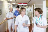 Female doctors discussing while colleagues in background at hospital corridor - MASF06458